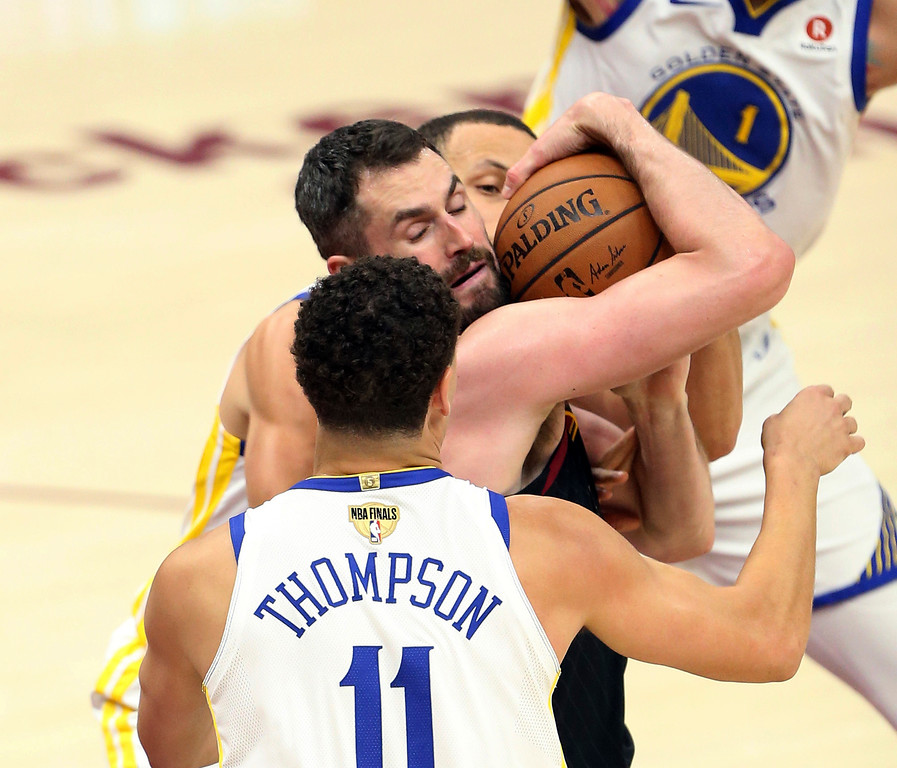 . Cleveland Cavaliers center Kevin Love fights for possession against Golden State Warriors guard Stephen Curry, rear, and guard Klay Thompson during the first half of Game 3 of basketball\'s NBA Finals on Wednesday, June 6, 2018, in Cleveland. (Joshua Gunter/Cleveland.com via AP)