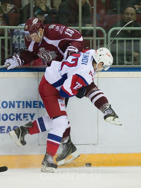 Emil Galimov (72) of Lokomotiv Yaroslavl checks Gunars Skvorcovs (13) in to the boards