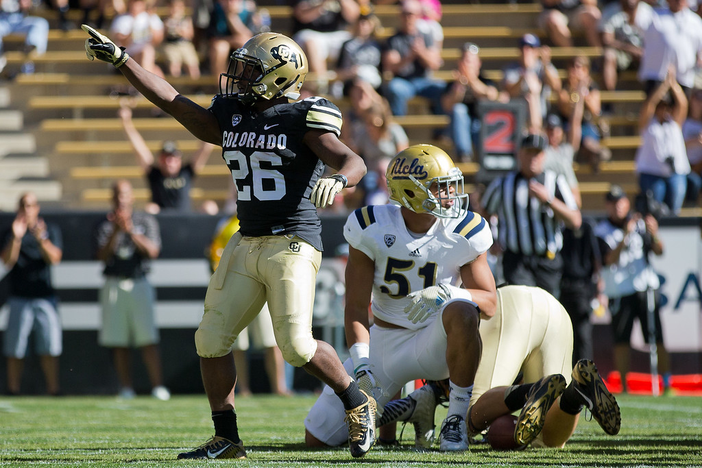 . BOULDER, CO - OCTOBER 25:  Running back Tony Jones #26 of the Colorado Buffaloes celebrates a touchdown run during the second quarter as linebacker Aaron Wallace #51 of the UCLA Bruins looks on at Folsom Field on October 25, 2014 in Boulder, Colorado. (Photo by Justin Edmonds/Getty Images)