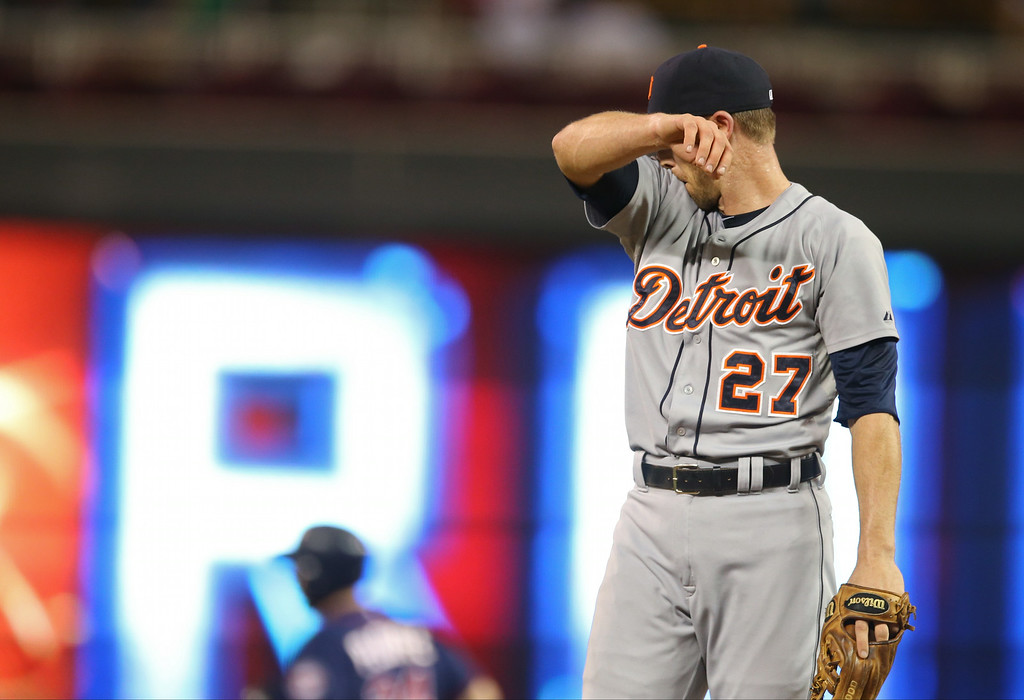 . Detroit Tigers shortstop Andrew Romine wipes his face after he have up a solo home run to Minnesota Twins\' Trevor Plouffe, while called upon to pitch in the eighth inning of a baseball game, Friday, Aug. 22, 2014, in Minneapolis. Romine also gave up a two-run home run to Twins\' Oswaldo Arcia moments earlier. The Twins won 20-6. (AP Photo/Jim Mone)