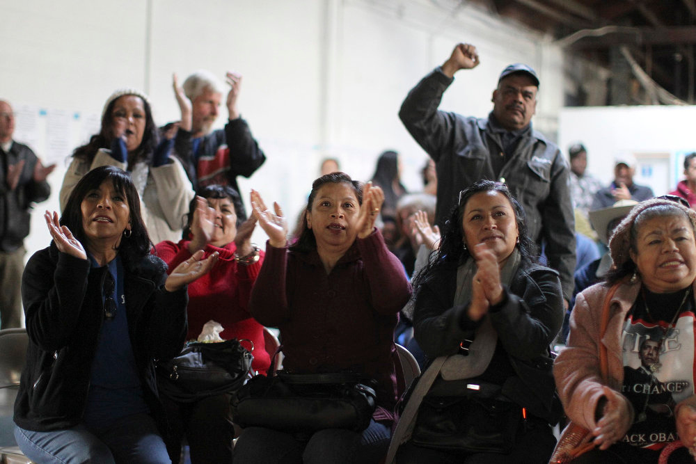 ". Black and Latino activists react as President Barack Obama takes the oath of office, in Gardena, California, January 21, 2013. President Barack Obama urged Americans on Monday to reject political ""absolutism\"" and partisan rancor as he kicked off his second term with a call for national unity, setting a pragmatic tone for the daunting challenges he faces over the next four years.  REUTERS/David McNew"