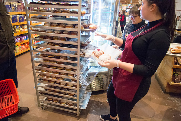 02/20/20 Wesley Bunnell | Staff Emily Krawczyski , R, picks out paczki for a customer from one of many large trays customers wait patiently in line at Roly Poly Bakery on Thursday February 20, 2020.