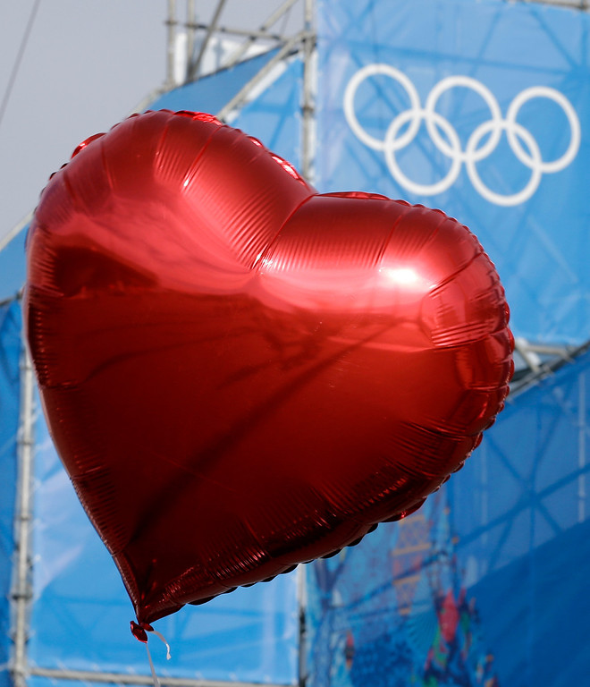 . A visitor to the Olympic Park carries a heart-shaped balloon on Valentine\'s Day at the 2014 Winter Olympics, Friday, Feb. 14, 2014, in Sochi, Russia. (AP Photo/David J. Phillip )