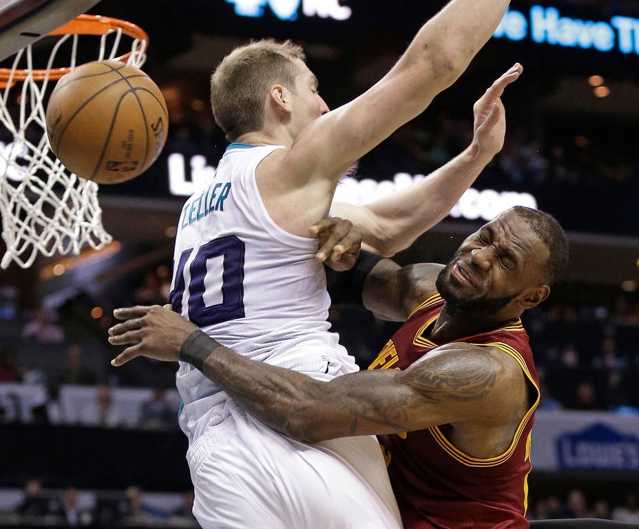 . Cleveland Cavaliers\' LeBron James, right, is fouled as he drives against Charlotte Hornets\' Cody Zeller, left, during the second half of an NBA basketball game in Charlotte, N.C., Friday, March 24, 2017. The Cavaliers won 112-105. (AP Photo/Chuck Burton)