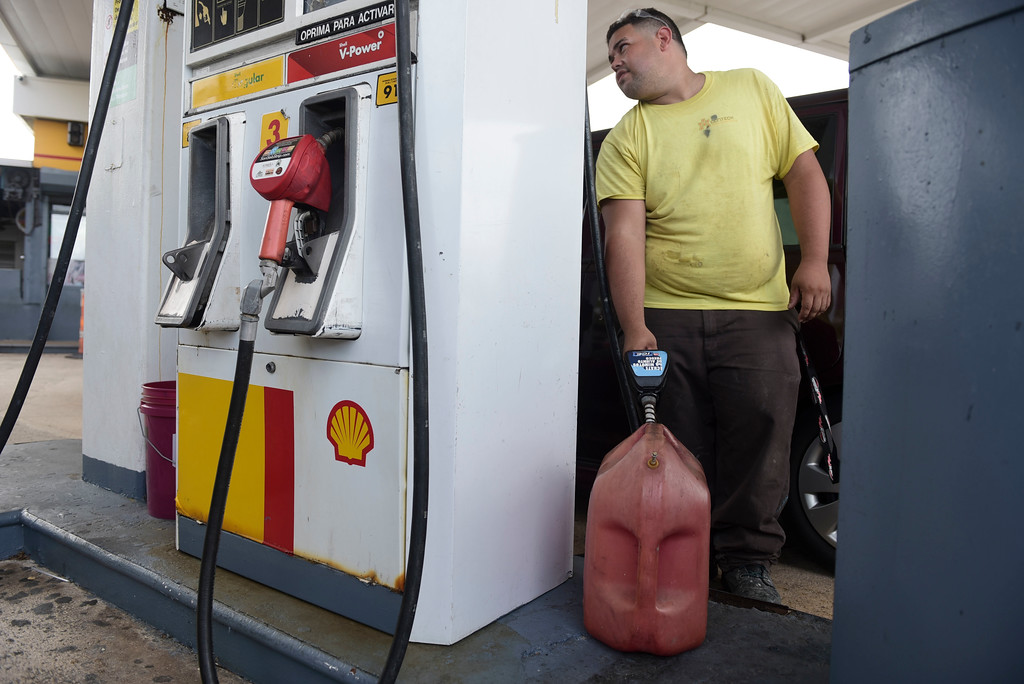 . Luis Fonseca fills a container with gasoline at a gas station one day before the forecasted arrival of Hurricane Maria in San Juan, Puerto Rico, Tuesday, Sept. 19, 2017. Authorities in the U.S. territory of Puerto Rico, which faces the possibility of a direct hit, warned that people in wooden or flimsy homes should find safe shelter before the storm�s expected arrival there on Wednesday. (AP Photo/Carlos Giusti)