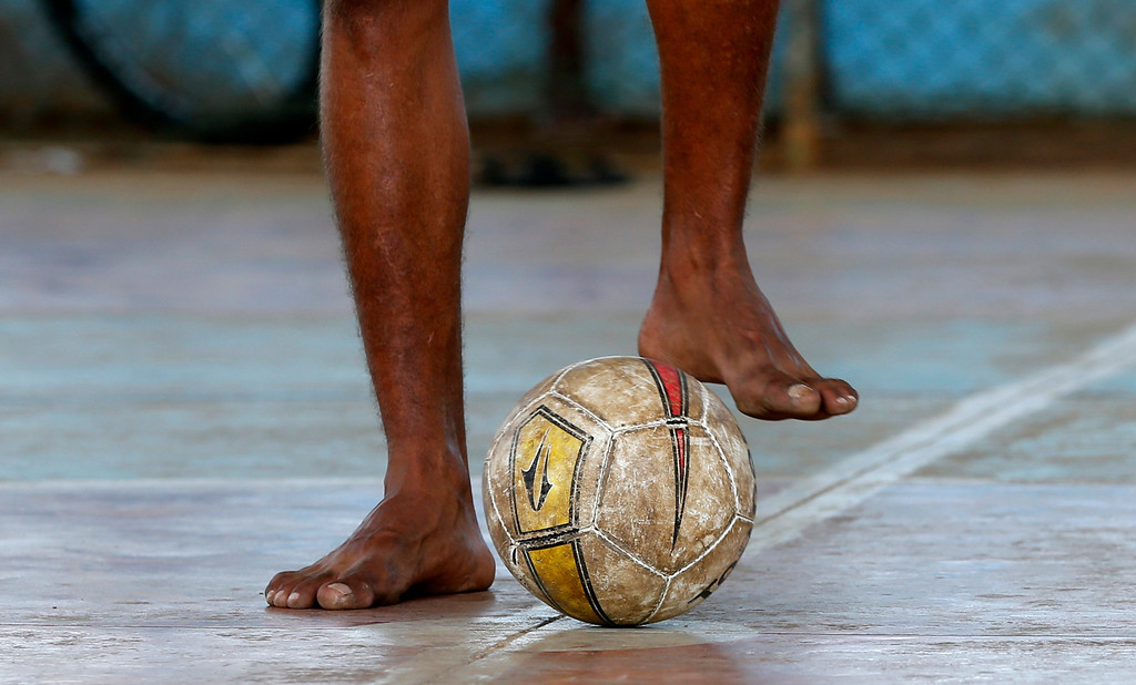 . In this Sunday, June 8, 2014 photo, a Brazilian boy dribbles a soccer ball as he waits for the start of the next street soccer game in a collapsing old hangar in Itu, on the outskirts of Sao Paulo, Brazil. A game is over after 10 minutes, or when one side scores two goals. The winner stays, the loser makes way for the next team. (AP Photo/Shuji Kajiyama)