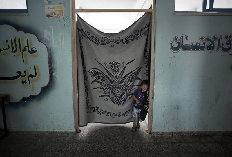 . In this Monday, July 14, 2014 photo, a boy waits at the entrance to a classroom of the New Gaza Boys United Nations School, where his family sought refuge after fleeing their home in fear of Israeli airstrikes. In Gaza, about one-fourth of the over 170 Palestinians killed in the past week were children, according to U.N. figures. (AP Photo/Khalil Hamra)