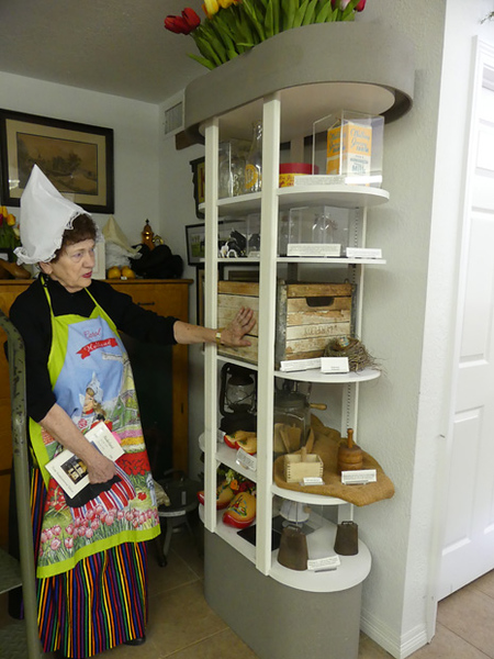 Woman dressed in Dutch garb explains items in the Windmill Museum.