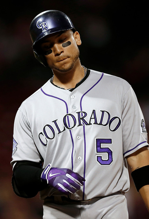 . Colorado Rockies\' Carlos Gonzalez heads back to the dugout after flying out during the ninth inning of the Rockies\' 11-4 loss to the Boston Red Sox in a baseball game at Fenway Park in Boston on Tuesday, June 25, 2013. (AP Photo/Winslow Townson)