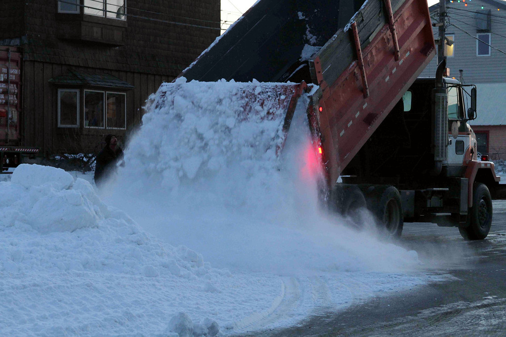 . A Nome public works truck dumps a load of snow onto Front Street on Sunday, March 9, 2014, in Nome, Alaska. The snow was trucked in to provide a trail for mushers to the finish line of the Iditarod Trail Sled Dog Race. (AP Photo/Mark Thiessen)