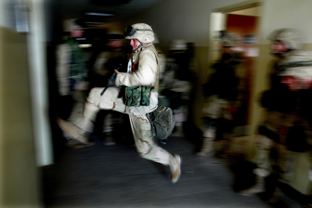 . US Marines kick in a door while securing a building next to the main hospital in central Baghdad April 15, 2003, which would be used as a temporary Iraqi police headquarters. REUTERS/Jerry Lampen