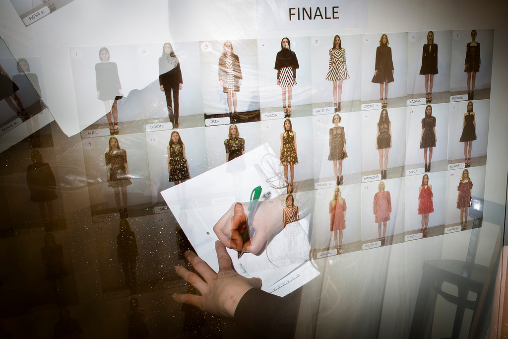 . In this photo made with multiple flash exposures, a volunteer makes notes beside a look board before the Jill Stuart Fall 2013 collection is shown at the Mercedes-Benz Fashion Week tents at Lincoln Center, Saturday, Feb. 9, 2013, in New York. (AP Photo/John Minchillo)