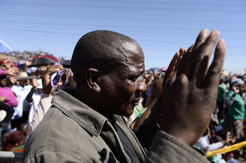 . Co-workers of 34 miners shot dead by South African police during a violent wage strike pray during a ceremony to mark the first anniversary of their deaths on August 16, 2013 in Marikana. Today marks a year after police opened fire on thousands of strikers at platinum producer Lonmin\'s mine, northwest of Johannesburg, which killed 34 and injured 78 people. The August shooting was described as the worst police brutality since the end of apartheid two decades ago. Three days ago, the firm has recognised radical labour group AMCU, which led the wage strike, in an attempt to ease simmering inter-union tensions on the platinum belt. STEPHANE DE SAKUTIN/AFP/Getty Images