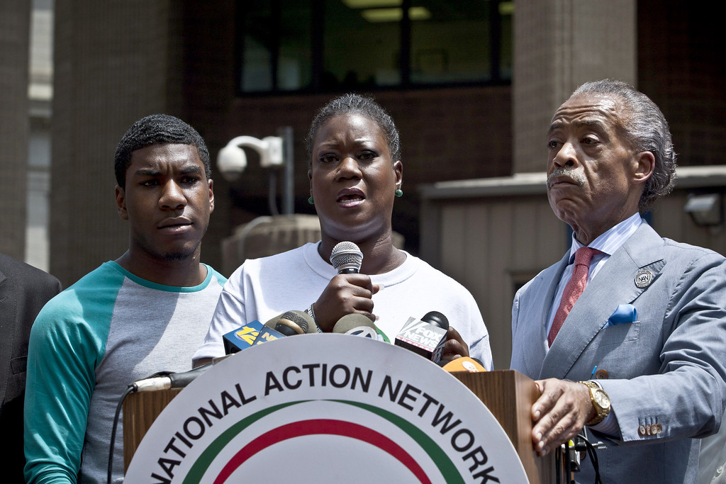. NEW YORK, NY - JULY 20:  Trayvon Martin\'s mother Sybrina Fulton speaks at a podium as Trayvon Martin\'s brother Jahvaris Fulton (L) and Rev. Al Sharpton attend a rally honoring Trayvon Martin organized by the National Action Network outside One Police Plaza in Manhattan on July 20, 2013 in New York City.  Demonstrators have gathered in various cities across the country to protest the acquittal of neighborhood watchman George Zimmerman and press for his federal prosecution in the shooting death of teenager Trayvon Martin.  (Photo by Kena Betancur/Getty Images)