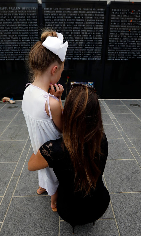 . Stephanie Gorman, holds her daughter Abby Grace Gorman, 10, as they take a private moment to look at their husband/father\'s name John Ballard Gorman, a Mississippi Gaming Commission agent, who was killed during a training exercise in 2015, listed on the Statewide Fallen Officers Memorial in Jackson, Miss., during the Mississippi Law Enforcement Memorial Candlelight Vigil, Tuesday, May 15, 2018. (AP Photo/Rogelio V. Solis)