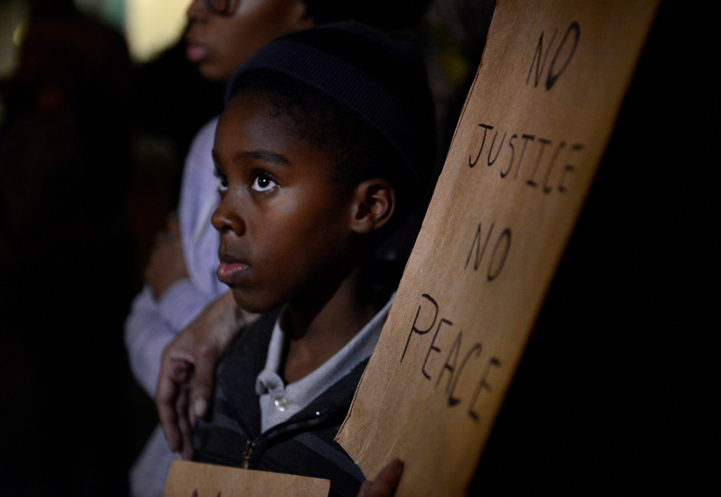 . Braylon Willis, 8, stands with protestors outside the Dallas Police Department headquarters in Dallas on Dec. 4, 2014. Dallas protestors joined others around the nation protesting in response to the lack of charges against a New York police officer who reportedly choked Eric Garner, an unarmed black man, which led to his death. (AP Photo/The Dallas Morning News, Rose Baca)