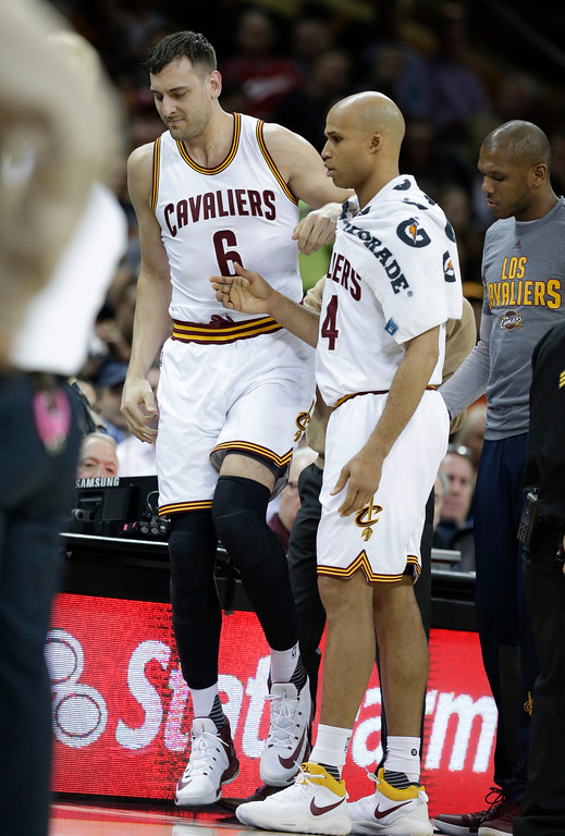 . Cleveland Cavaliers\' Andrew Bogut (6) is helped up by Cleveland Cavaliers\' Richard Jefferson (24) in the first half of an NBA basketball game against the Miami Heat, Monday, March 6, 2017, in Cleveland. Initial X-rays and evaluation of Bogut revealed a fractured left tibia. The Heat won 106-98. (AP Photo/Tony Dejak)