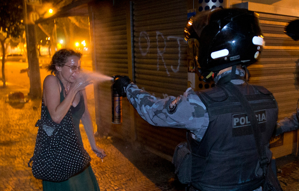 . A military police pePper sprays a protester during a demonstration in Rio de Janeiro, Brazil, Monday, June 17, 2013. Protesters massed in at least seven Brazilian cities Monday for another round of demonstrations voicing disgruntlement about life in the country, raising questions about security during big events like the current Confederations Cup and a papal visit next month. ((AP Photo/Victor R. Caivano)