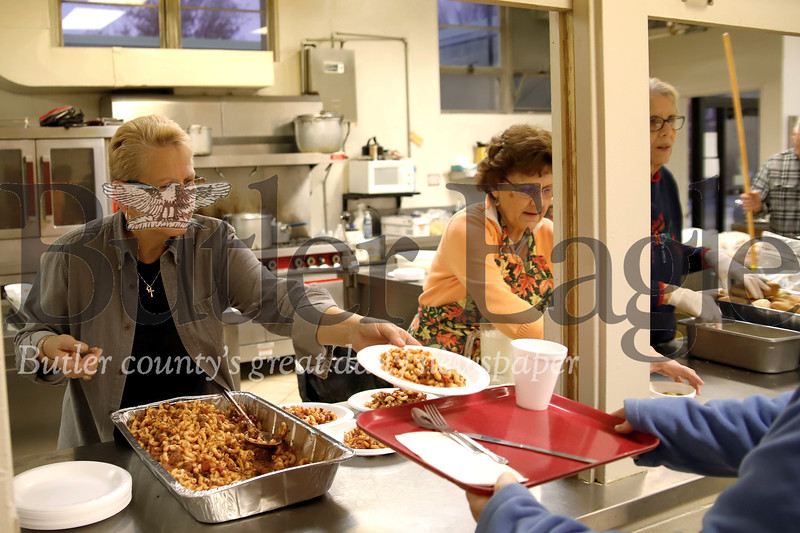Jan Stirling-Kelly (left), Lynne Updegraff and other volunteers serve up donated ground venison macaroni made by First United Methodist Church chef Ray Christy at the church's weekly community dinner Friday night. Seb Foltz/Butler Eagle