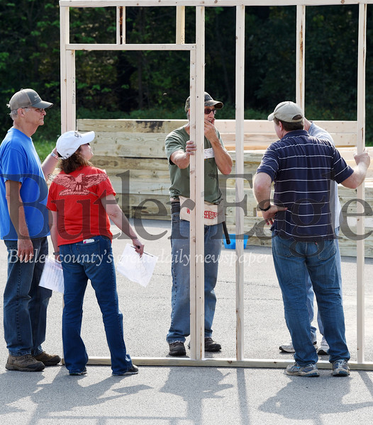 Harold Aughton/Butler Eagle: (right - left) Bruce and Sue Burtner, Roy Koegler, brothers, Arlin and Steve Rummel, examine the wall they built as part of a missionary project at St. Luke Lutheran Church Sat. Sept. 21.