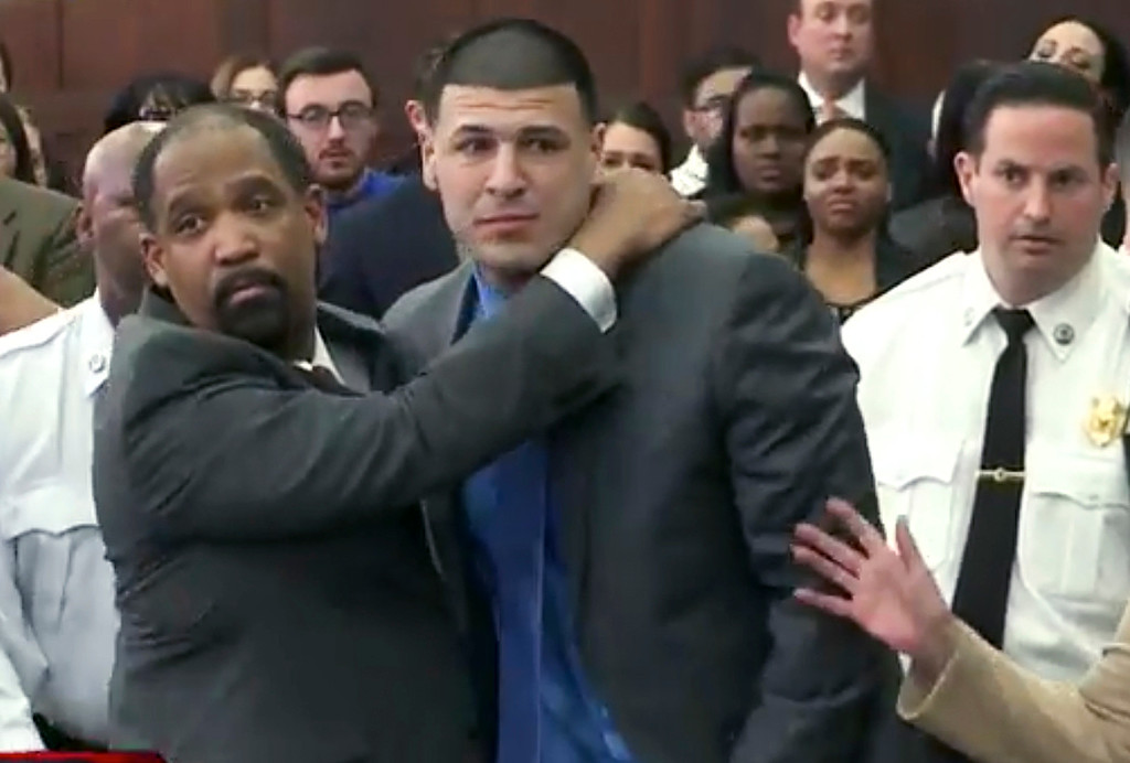 . In this still image from video, Aaron Hernandez, center, is hugged by defense attorney Ronald Sullivan Friday, April 14, 2017, in court in Boston, after being found not guilty of murder in the 2012 shootings of two men in a drive-by shooting in Boston. (WHDH-TV via AP, Pool)