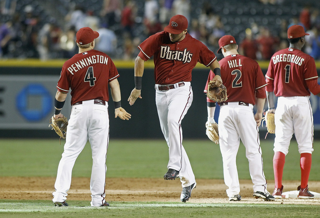 . Cliff Pennington #4 and David Peralta #6 of the Arizona Diamondbacks celebrate a 6-2 victory against the Colorado Rockies during a MLB game at Chase Field on August 31, 2014 in Phoenix, Arizona.  (Photo by Ralph Freso/Getty Images)