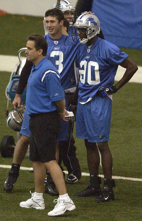 . Detroit Lions QB Joey Harrington (3) pats wide receiver Charles Rogers (80) on the head after he made a tough catch as head coach Steve Mariucci watches play during Thursday\'s mini-camp held at the Detroit Lions practice facility in Allen Park