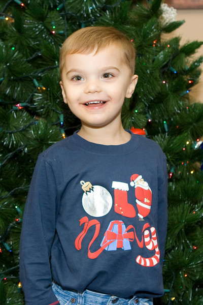 K.C. is posing in front of our Christmas tree.