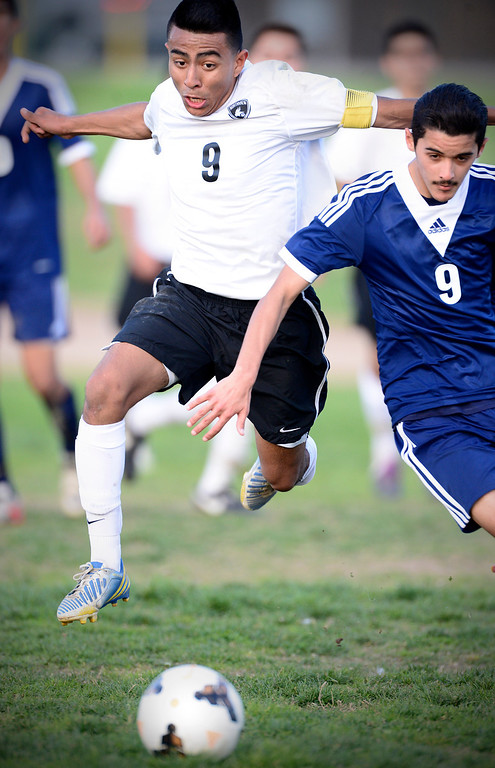 . Northview\'s Christian Palacios (9) and Baldwin Park\'s Eduardo Suarez (9) trail the ball as Baldwin Park defeats Northview 2-0 during Tuesday\'s game at Northview High School, February 11, 2014. (Photo by Sarah Reingewirtz/Pasadena Star-News)