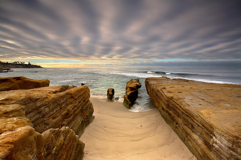 Since rock and sand are such important elements in the seascape, choosing a memorable vantage point can be crucial to the creation of a good photograph.  I spotted the amazing cloud formation first, and then I looked around and found a spot where the sandstone formations lined up with the cloud patterns. I had to run quite a way down the beach to get here just in case the alignment were to disappear.  Then I waited for a wave to complement the scene and provide definition to the sandstone formation on the right side of the frame.  I have never seen anything like this before or after, so I was quite fortunate!