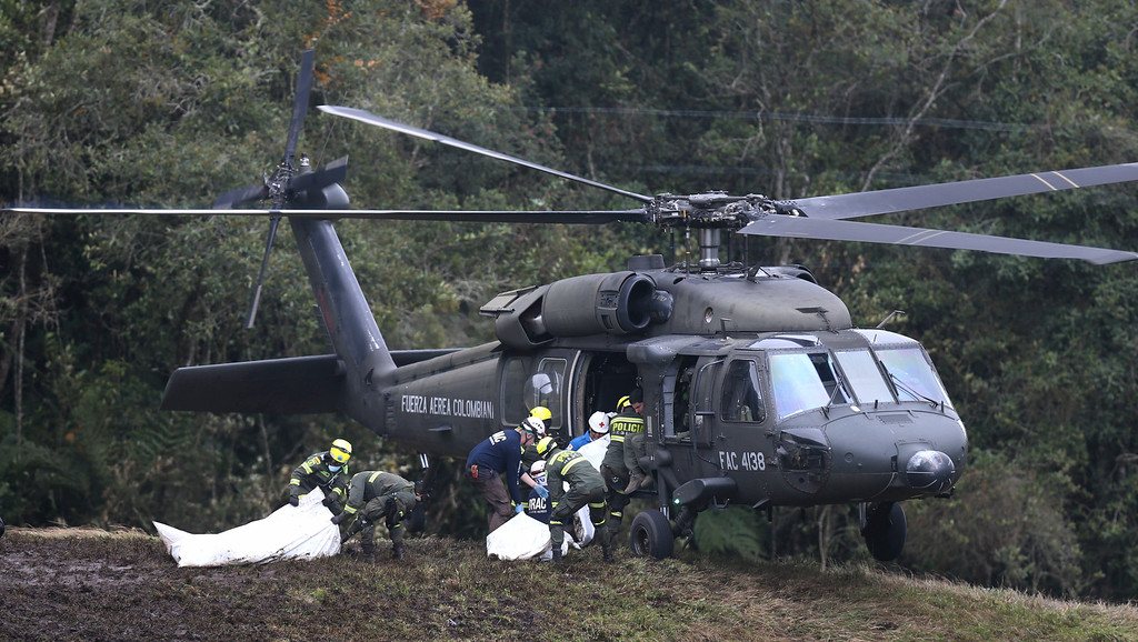 . Rescue workers place the bodies of victims of an airplane crash into a waiting helicopter, in La Union, near Medellin, Colombia, Tuesday, Nov. 29, 2016. The chartered plane was carrying a Brazilian soccer team to the biggest match of its history when it crashed into a Colombian hillside and broke into pieces, killing 75 people and leaving six survivors, Colombian officials said Tuesday. (AP Photo/Fernando Vergara)
