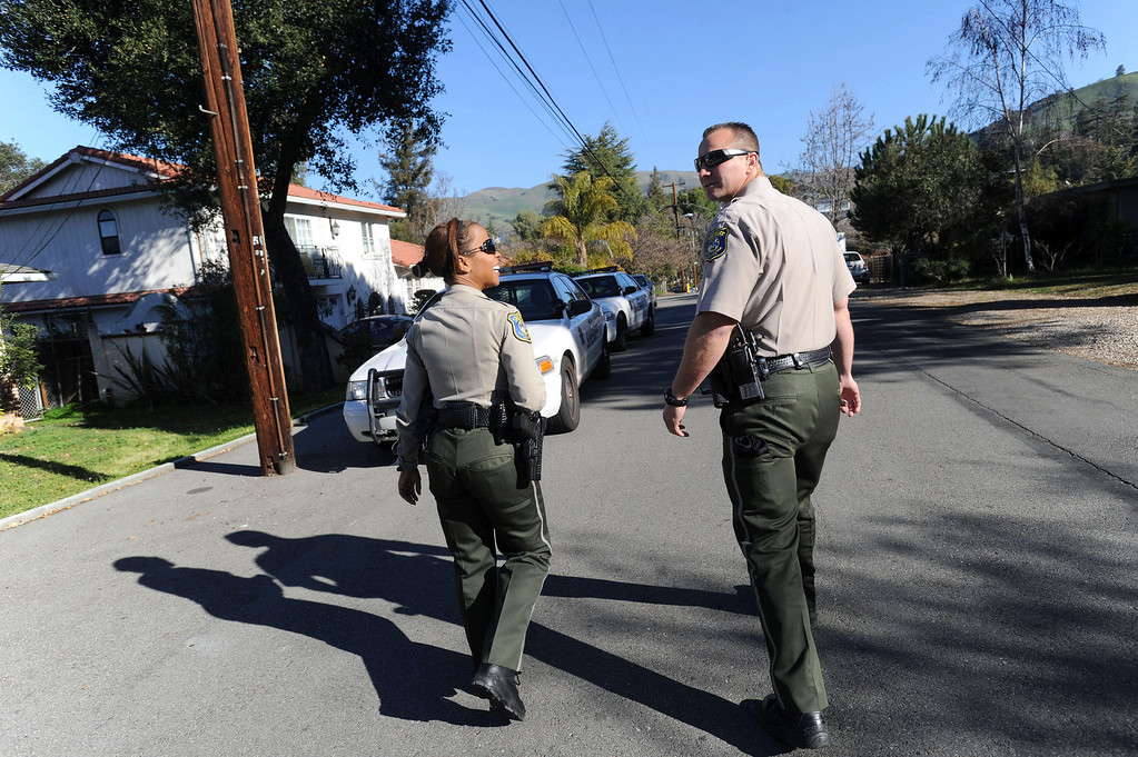 . Santa Clara County Sheriff\'s deputies Ryan Griep, left, and Dessaure (she did not want her first name used), right, plan their next stop in an unincorporated portion of East San Jose, Calif. on Monday, Feb. 11, 2013. The Santa Clara County Sheriff\'s Office is increasing its efforts to take once lawfully owned firearms from those who can no longer own them due to more recent circumstances in their lives. Officers are attempting to make contact with these people and ask them to voluntarily turn over any firearms. A monthly list of these people is put out by the Department of Justice. (Dan Honda/Staff)