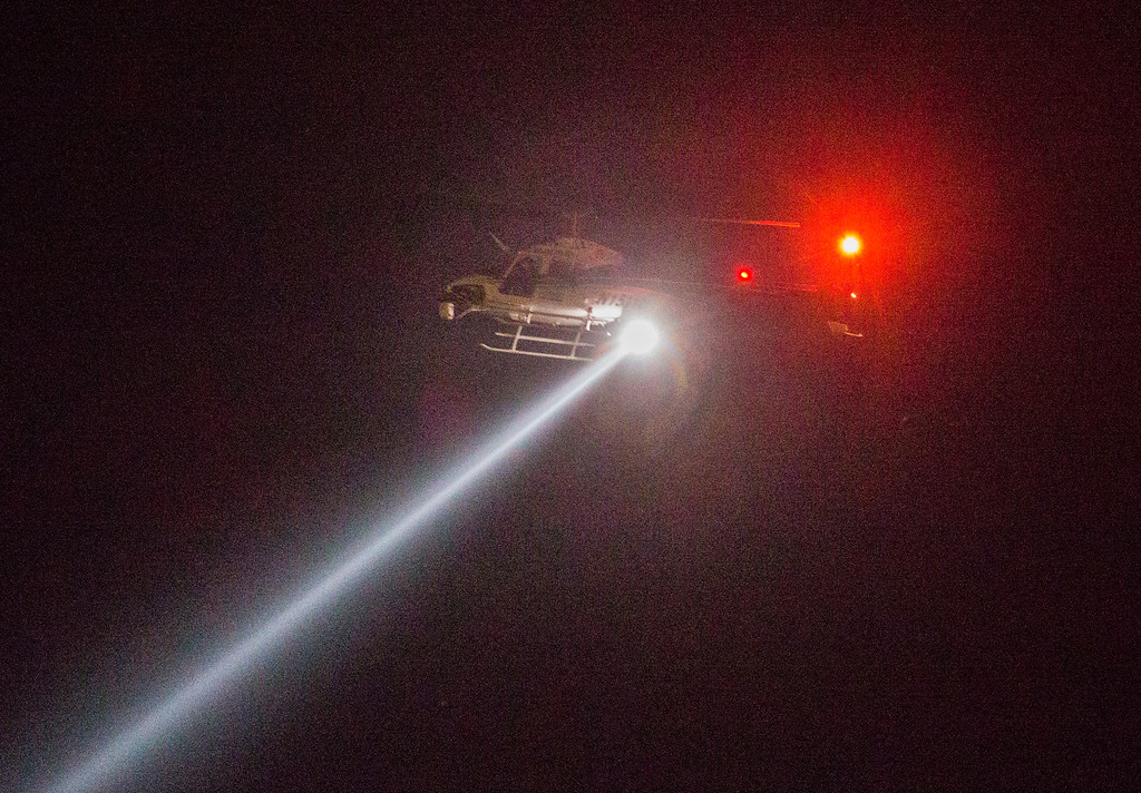 . A helicopter with a search light circles as police officers gather at the intersection of Interstate 20 and E Palestine Street, where police have cornered a suspect in a van on Saturday, June 13, 2015 in Hutchins, Texas.   Police Chief David Brown says a police sniper has shot the suspect in an overnight attack on police headquarters and that the department is checking to see if he\'s still alive. Brown says investigators believe the man acted alone in the early-morning attack on Dallas police headquarters, despite early witness reports that others may have taken part.   (Ashley Landis/The Dallas Morning News via AP)