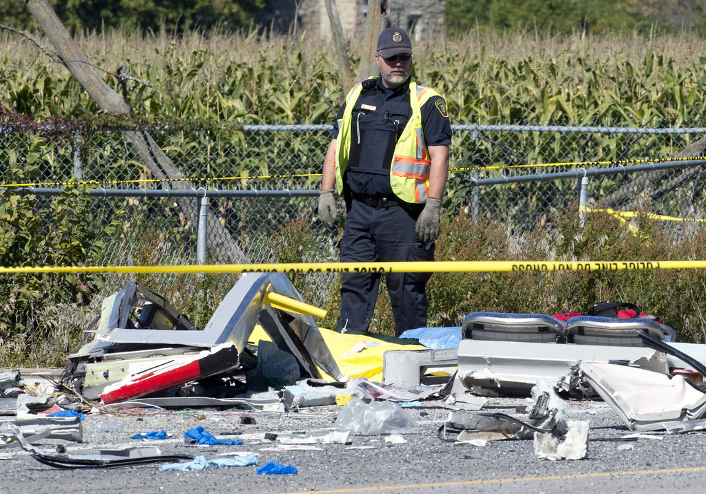 . An emergency worker looks over the debris from a collision between a city bus and Via Rail train, Wednesday Sept. 18, 2013 in Ottawa, Canada. Witnesses said the bus went through a closed crossing barrier. (AP Photo/The Canadian Press, Adrian Wyld)