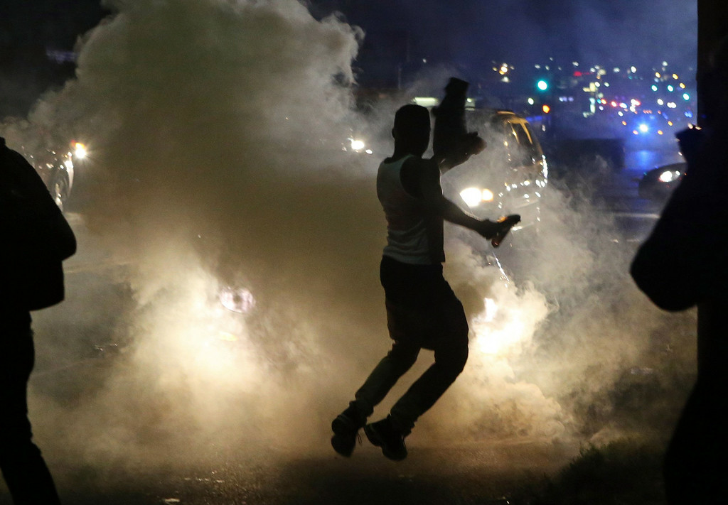 . Protesters run when the police shoot tear gas in Ferguson, Mo., Sunday, Aug. 17, 2014. Protests over the killing of 18-year-old Michael Brown by a white police officer have entered their second week. (AP Photo/St. Louis Post-Dispatch, J.B. Forbes)