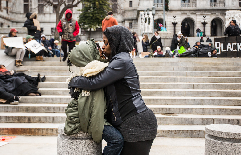 . Chanelle neal kisses her son Jamar, 8,  on the steps of the Pennsylvania State Capitol in Harrisburg, Saturday, Dec. 13, 2014,  in protest of police abuses in the black community. (AP Photo/PennLive.com, James Robinson)