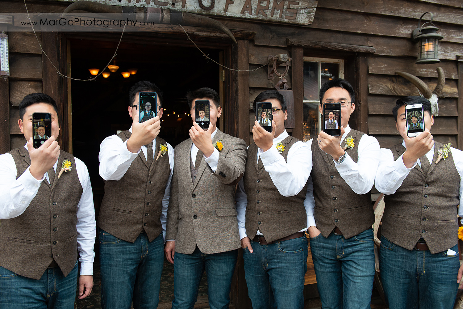 groom and groomsmen lineup with their portraits on the phones at Long Branch Saloon & Farms in Half Moon Bay