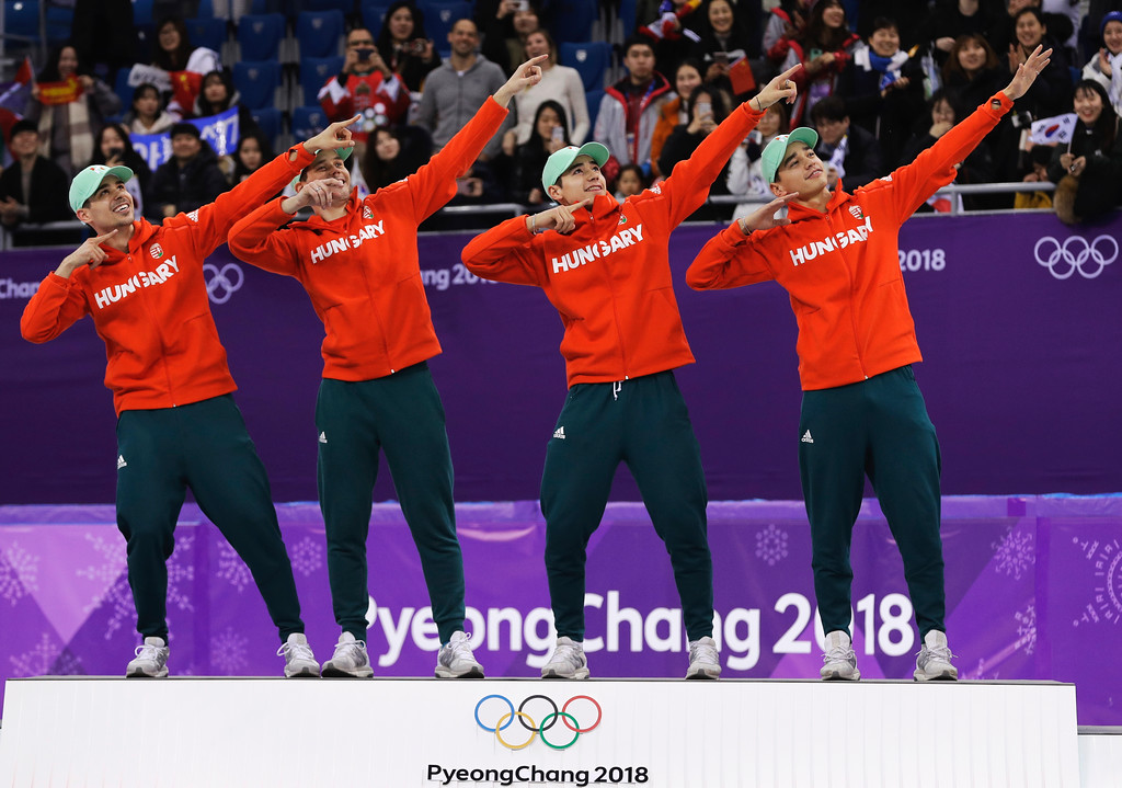 . Hungary men\'s 5000 meters short track speedskating relay final team, from left, Csaba Burjan, Viktor Knoch, Liu Shaoang and Liu Shaolin Sandor celebrate on the podium after winning the gold medal in the Gangneung Ice Arena at the 2018 Winter Olympics in Gangneung, South Korea, Thursday, Feb. 22, 2018. (AP Photo/David J. Phillip)