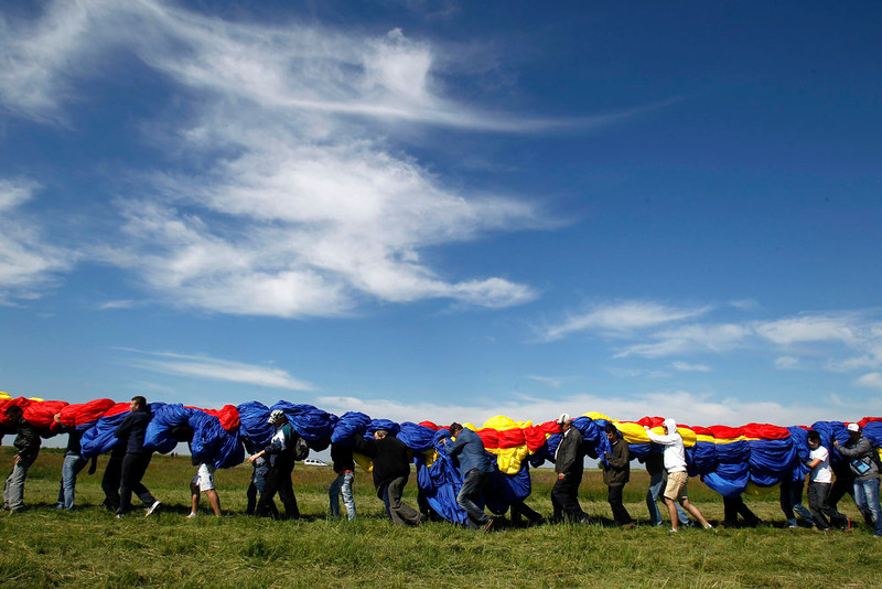 . Workers carry Romania\'s national flag during a Guinness World Record attempt for the world\'s biggest national flag in Clinceni, near Bucharest May 27, 2013. The flag, measuring 349.4 per 226.9 meters, established a new Guinness World Record, according to the organization\'s officials. REUTERS/Bogdan Cristel
