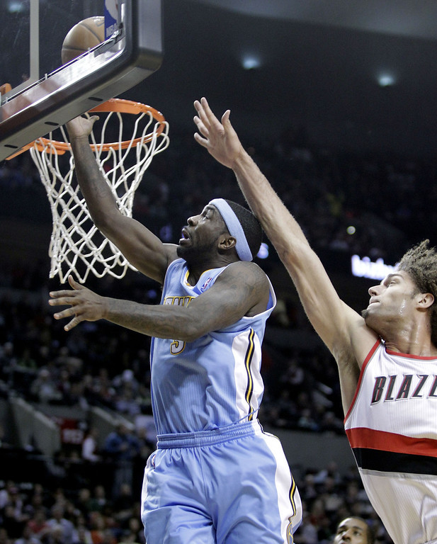 . Denver Nuggets guard Ty Lawson, left, goes to the hoop past Portland Trail Blazers center Robin Lopez during the first half of an NBA basketball game in Portland, Ore., Thursday, Jan. 23, 2014. (AP Photo/Don Ryan)