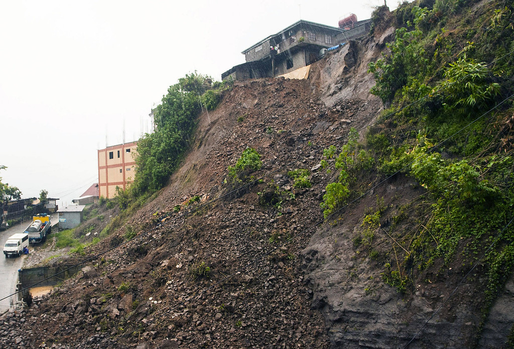 . The soil is exposed at the site of a landslide in Baguio city as powerful typhoon Utor batters the northern Philippines Monday, Aug. 12, 2013, toppling power lines and dumping heavy rain across mountains, cities and food-growing plains. The storm killed at least one man in a landslide and left 45 fishermen missing. Typhoon Utor, described as the strongest globally so far this year, slammed ashore in mountainous eastern Aurora province with sustained winds of 175 kilometers (109 miles) per hour and gusts of up to 210 kph (130 mph). (AP Photo)