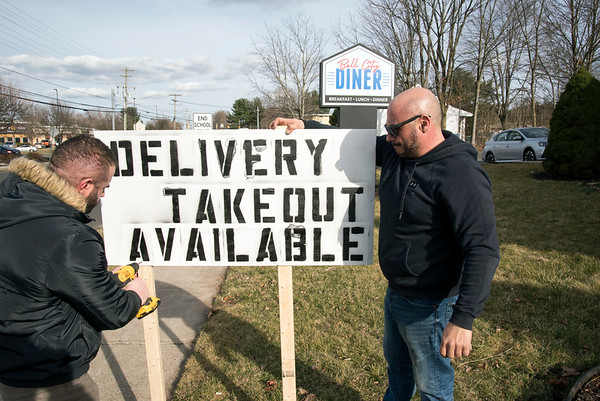 dS03/27/20 Wesley Bunnell | StaffrrBell City Diner manager Louie Elezovski, L, works with manager Peter Pavlodis in putting up a temporary sign informing the public of take out and delivery options on Monday afternoon. empty Bell City Restaurant on Monday afternoon. Health officials shut down all state restaurants at 8p.m. to dining inside while still allowing them to offer deliver and offer to go service.