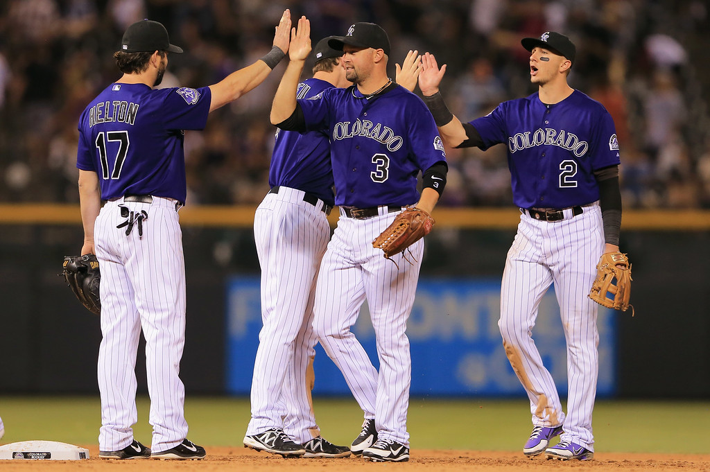 . DENVER, CO - JULY 26:  Todd Helton #17, Michael Cuddyer #3, DJ LeMahieu #9 and Troy Tulowitzki #2 of the Colorado Rockies celebrate their 8-3 victory over the Milwaukee Brewers at Coors Field on July 26, 2013 in Denver, Colorado.  (Photo by Doug Pensinger/Getty Images)