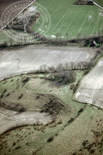 Farmland west of Ravlunda church - with plantations, buildings and prehistoric remains (2 April, 1989). | LH.0530