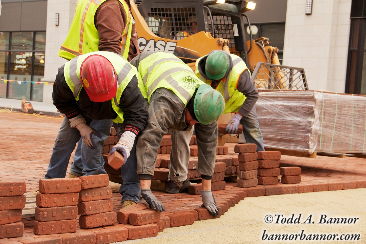 Construction workers lay paving bricks during Marion Street reconstruction project on Saturday November 19, 2011 in Oak Park, Illinois,  USA.  Brick is being used to return the street to its early 20th century appearance and reduce storm runoff.