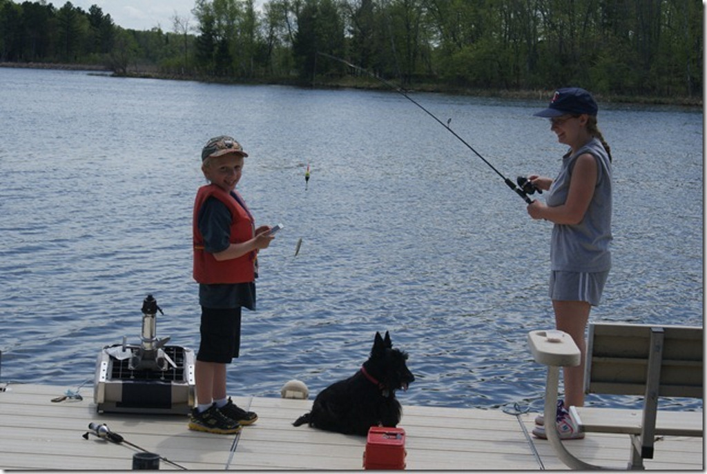 . Dennis Forsberg photographed his grandkids, Nate Forsberg, 6, and Anna Forsberg, 16, both of Menahga fishing off his dock on Third Crow Wing Lake May 30 with dog Lacy. (Photo courtesy Dennis Forsberg)