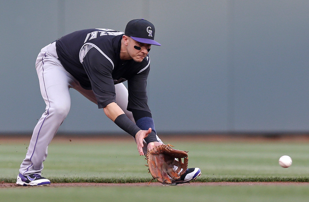 . Colorado Rockies shortstop Troy Tulowitzki fields a ground ball hit by Cincinnati Reds\' Brayan Pena in the first inning of a baseball game, Saturday, May 10, 2014, in Cincinnati. Tulowitzki threw Pena out at first. (AP Photo/Al Behrman)