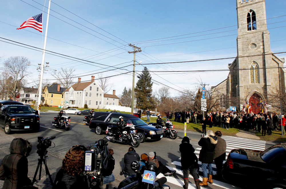 . While media, bottom, watch the mourners, right, gather outside of Trinity Episcopal Church during funeral services for Benjamin Andrew Wheeler, one of the students killed in the Sandy Hook Elementary School shooting last week, a hearse with another shooting victim rides through during a procession, Thursday, Dec. 20, 2012, in Newtown, Conn. The victims died when the gunman, Adam Lanza, walked into Sandy Hook Elementary School in Newtown, Conn., Dec. 14, and opened fire, killing 26 people, including 20 children, before killing himself. (AP Photo/Julio Cortez)