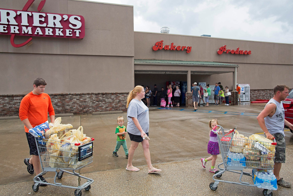 . Eli Turnage, 14, left, helps the Creel family, from left to right, Addison, Jessica, Brantley, and Thomas with their groceries in the parking lot of Carter\'s Supermarket in Livingston, La., Monday, Aug. 15, 2016. Turnage is volunteering at the supermarket to keep himself busy after his home was destroyed from the flooding. The Creel family was stocking up before returning to their flood damaged home. (AP Photo/Max Becherer)