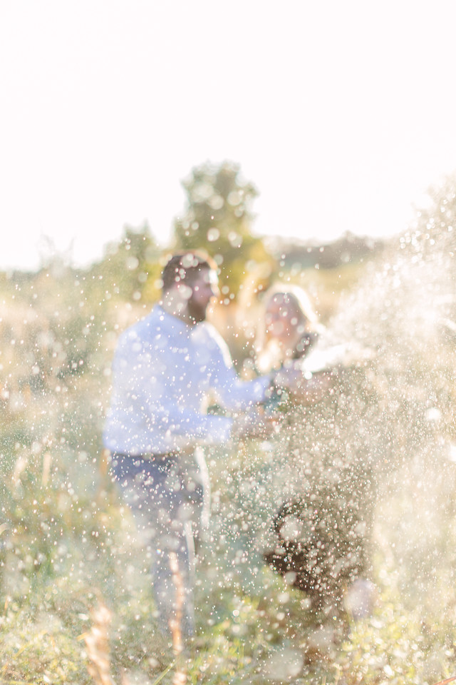 Spraying the photographer with champagne at their field engagement session in Virginia.